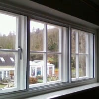 White aluminium secondary glazing face fixed into existing timber window.