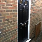 Black GRP Composite front door with a white uPVC outerframe and chrome furniture