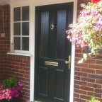 Green GRP Composite front door with a white uPVC outerframe, sidelight with surface mounted Georgian Bars and gold furniture