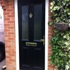 Black GRP Composite front door with a white uPVC outerframe and gold furniture