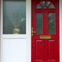 Red GRP Composite front door with a white uPVC outerframe, sidelight and gold colour furniture