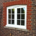 White painted hardwood windows with surface mounted Georgian Bars, Monkey Tail handles and a 4000 trickle vent in the head frame