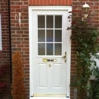 White GRP Composite front door with a white uPVC outerframe and gold furniture