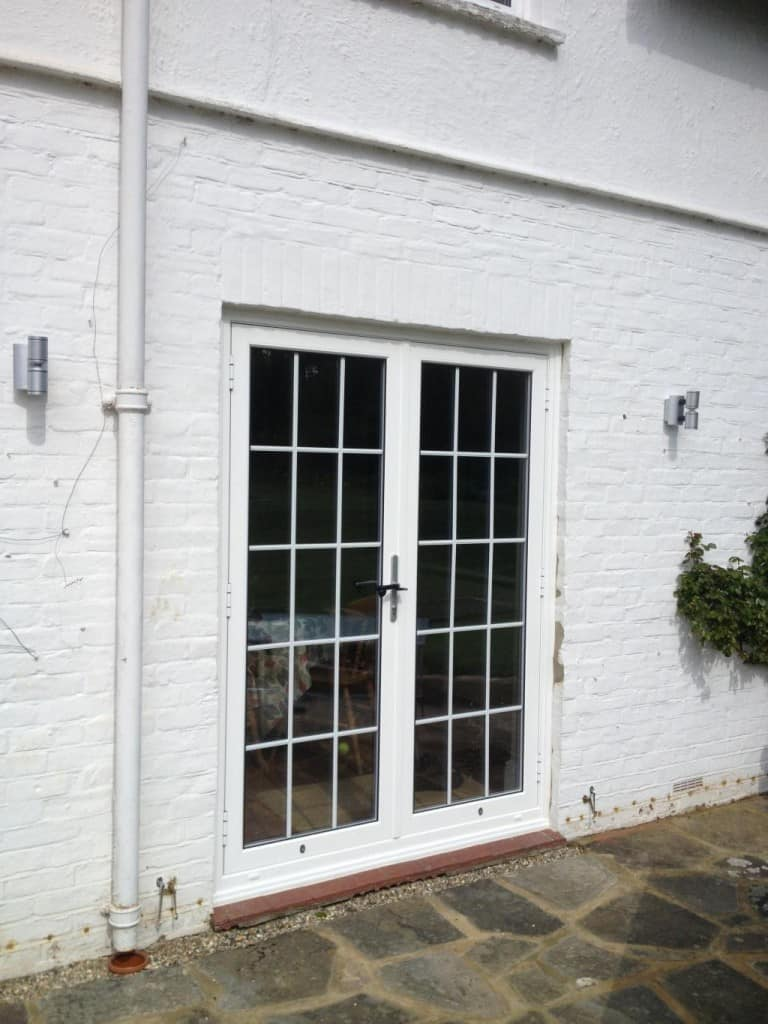 Aluminium french doors with 18mm internal Georgian Bars installed directly into brickwork with a stained hardwood cill