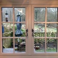 A-rated White uPVC window with fully sculptured framing, surface mounted Georgian Bars and black antique style monkeytail handles