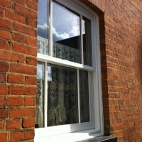 White painted hardwood sliding sash window with surface mounted Georgian Bars