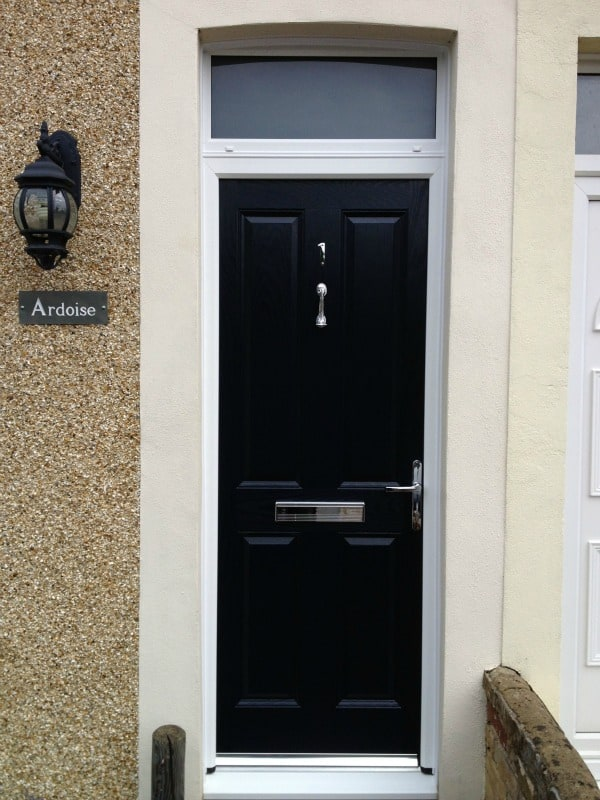 Black GRP composite front door with sandblasted (satin) glass in top light and a chrome pony tail knocker, letterbox and handle.   (2)