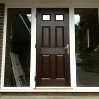 Darkwood GRP composite front door with white a uPVC outerframe glazed with clear toughened glass